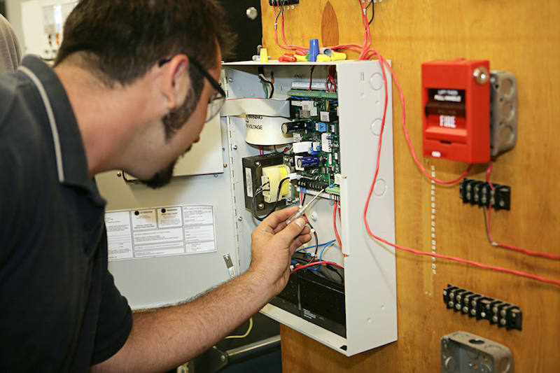 A man installing a fire alarm system