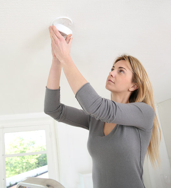 woman installing fire alarm